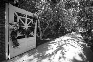 black-and-white-photo-of-long-driveway-and-gate