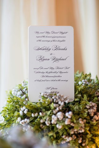 a-couples-white-wedding-invitation-standing-up-on-base-of-green-foliage-with-small-berries