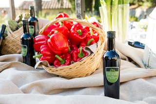 table-decorated-with-bright-red-bell-peppers-in-a-basket-and-bottles-of-olive-oil