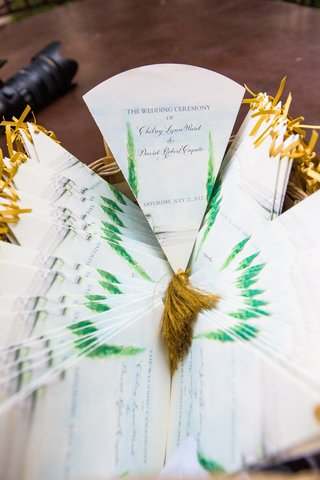 wedding-ceremony-programs-in-the-form-of-fans-with-watercolor-paintings-of-trees-and-gold-tassels