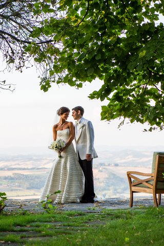 bride-in-a-strapless-vera-wang-gown-with-champagne-bands-with-groom-in-tuxedo-with-white-coat