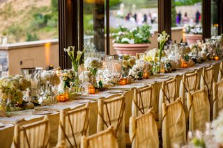 wedding-reception-table-with-white-flowers-in-mercury-and-glass-vases-lined-along-the-middle