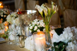 wedding-reception-table-decorated-with-white-flowers-candles-and-mercury-vessels