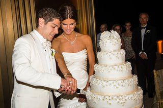 bride-in-a-vera-wang-gown-and-groom-a-white-tuxedo-coat-cut-white-wedding-cake-with-flowers