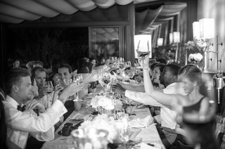black-and-white-photo-of-guests-toasting-at-a-wedding-reception-dinner