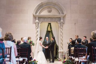 ceremony-in-great-hall-art-institute-of-dayton-venue-wedding-ohio-fabric-curtain-greenery-couple