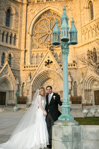 bride-in-a-pnina-tornai-dress-with-long-sleeve-illusion-neckline-veil-groom-in-black-morning-coat