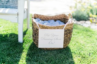 light-blue-flip-flops-in-wicker-basket-with-sign-attached-in-ribbon-for-dancing-at-wedding