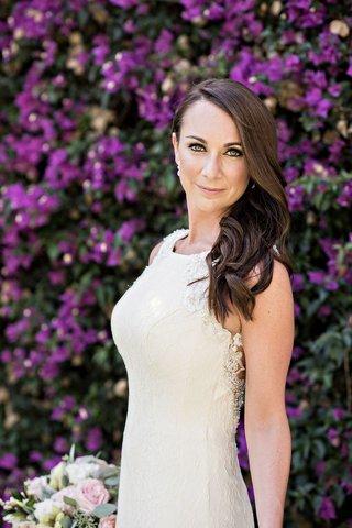 bride-lace-sheath-dress-posing-flower-wall-wedding-bouquet-white
