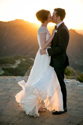 bride-in-reem-acra-wedding-dress-blowing-in-wind-kisses-groom-in-suit-on-helipad-malibu-rocky-oaks