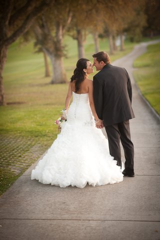 bride-in-a-maggie-sottero-dress-with-ruffled-skirt-holds-hands-with-groom-in-black-tuxedo