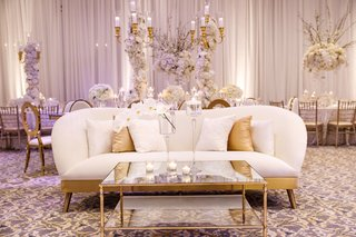 wedding-reception-lounge-seating-area-white-gold-sofa-curved-gold-mirror-coffee-table-candles-orchid