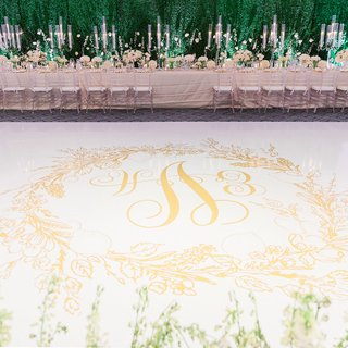 white-dance-floor-with-gold-monogram-surrounded-by-gold-wreath