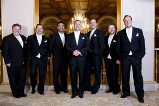 groomsmen-in-black-tuxedos-with-white-tie-and-pocket-square
