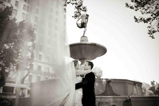 black-and-white-photo-of-couple-with-veil-in-wind