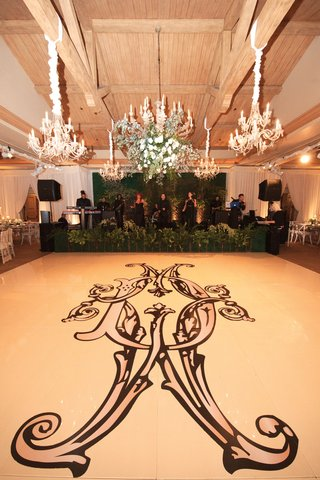dance-floor-with-large-ornate-monogram-in-black-chandeliers-above