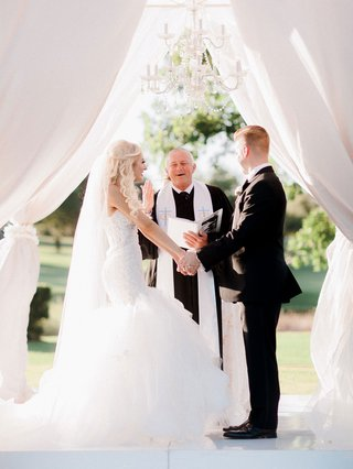 bride-in-strapless-trumpet-gown-with-groom-holding-hands-during-outside-ceremony-christian-wedding