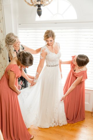 bride-in-wedding-dress-lace-long-illusion-sleeves-bridesmaids-helping-skirt-mother-of-bride