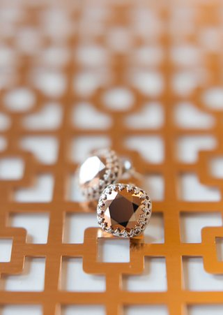 copper-jewel-earrings-on-top-of-a-geometric-design-in-the-same-color