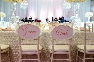 head-table-with-bride-and-groom-chairs-pink-sign-with-ivory-flower-petals-around-border-flower-petal