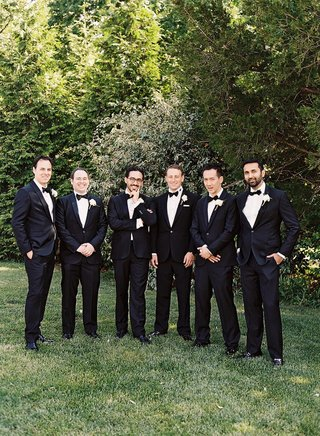 men-in-tuxedos-and-bow-ties-standing-on-grass