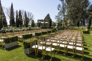 manicured-hedges-and-gold-chairs-on-grass-lawn