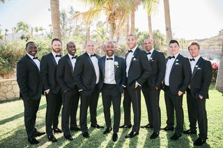 a-groom-in-a-blue-and-black-tuxedo-stands-groomsmen-classic-black-tuxedos-outdoor-near-palm-trees