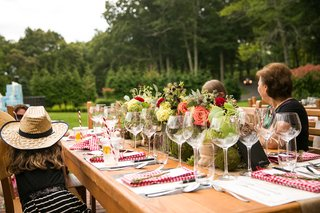 wedding-shower-guests-at-wooden-table-with-flower-runner