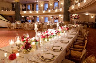 long-wedding-reception-table-with-candles-low-flower-arrangements-gold-details-by-dance-floor