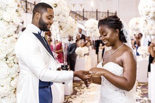bride-and-groom-exchanging-rings-at-castle-wedding-ceremony-royal-wedding-attire-white-flowers