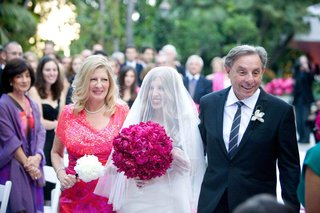 bride-with-veil-over-face-walking-down-aisle-with-parents