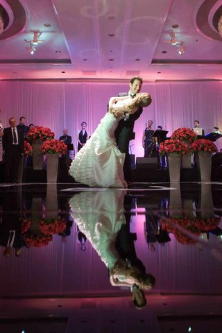 groom-dips-bride-on-dance-floor-with-reflection