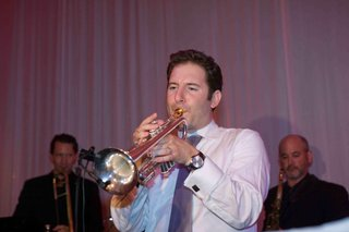 groom-in-white-button-up-and-tie-with-trumpet
