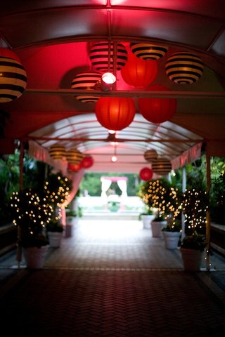 red-lighting-in-tunnel-entryway-with-striped-paper-lanterns