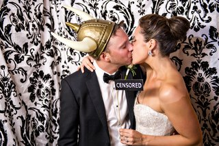 bride-kisses-groom-with-censored-sign-in-damask-print-photobooth