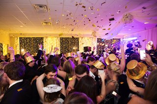 wedding-guests-on-dance-floor-in-new-years-eve-tiaras-and-party-hats-with-gold-confetti-in-air