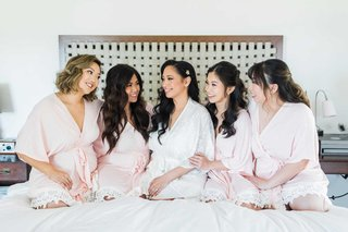bride-in-white-robe-with-bridesmaids-on-bed-in-pink-robes-with-lace-hem