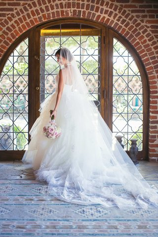 bride-in-white-tulle-ball-gown-with-plunging-halter-neckline-posing-to-show-off-back-of-dress-veil