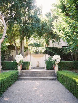 green-courtyard-white-floral-arrangements-shrubbery-altar-in-outdoor-ceremony-space-estate