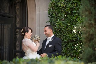 bride-in-gold-ball-gown-with-jewel-bouquet-smiles-with-groom-during-first-look-in-courtyard