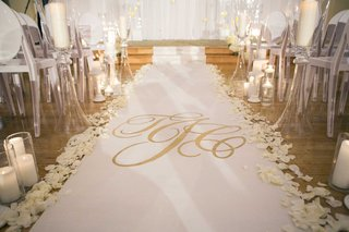 white-aisle-runner-with-gold-monogram-by-the-original-runner-co-with-candles-and-flower-petals