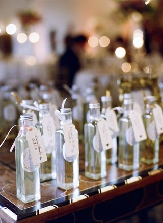 escort-cards-attached-with-ribbon-to-miniature-bottles-of-limoncello-made-by-the-groom-wedding-favor