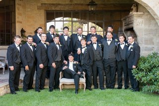 groom-in-armchair-with-white-bow-tie-surrounded-by-groomsmen-in-tuxedos-and-bow-ties