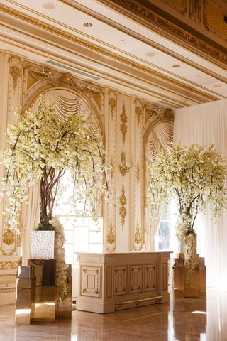 white-flowers-on-tall-tree-by-wedding-bar-white-and-gold-bars