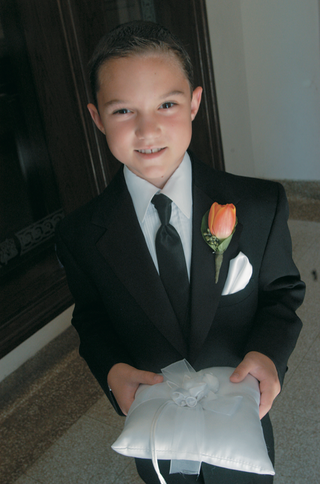 ring-bearer-wears-orange-tulip-boutonniere-and-carries-white-pillow