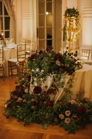 wedding-reception-sweetheart-table-moody-burgundy-flowers-greenery-draping-cascading-down-linens