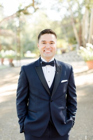 smiling-groom-in-midnight-blue-tuxedo-with-his-hands-in-his-pockets
