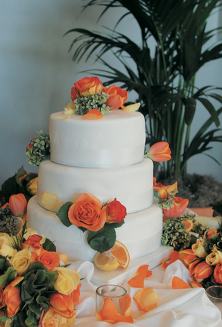orange-roses-and-lemon-and-orange-wedges-adorn-white-cake