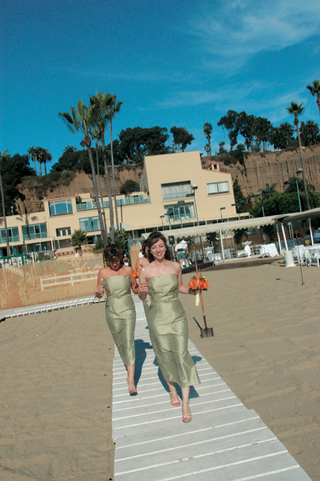 two-bridesmaids-in-green-dresses-walk-on-wood-plank-aisle-on-sand