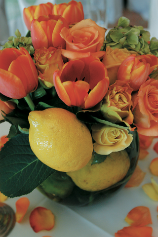 glass-bowl-filled-with-orange-tulips-and-roses-and-lemons